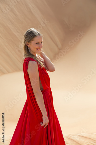 Tuinposter Abu Dhabi woman in a red dress in a desert in Abu Dhabi
