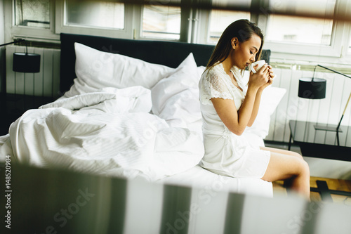 Plagát Young woman drinking coffee in the bed
