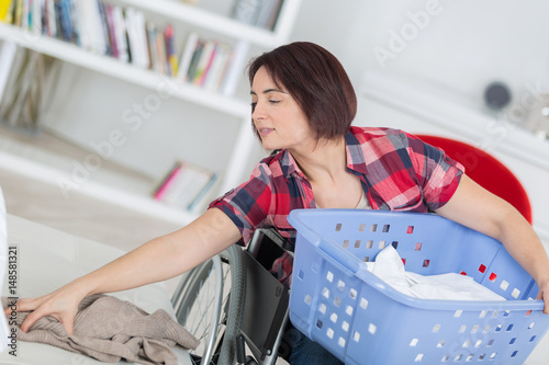 disabled woman doing her laundry at home Poster