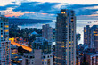 Vancouver Canada aerial city view at colorful sunset. Illuminated skyscrapers and the bay is shown in the background