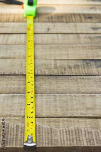Poster tape measure on the brown wooden background