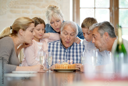 Poster Family celebrating grandfather birthday with cake and candles