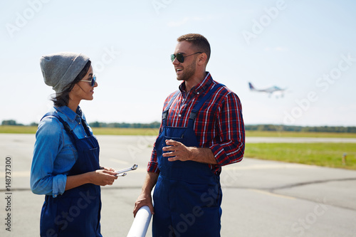 Poster Portrait of two modern mechanics, man and woman, standing in airport runway fiel