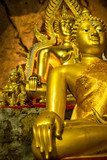 Gold Buddha meditating in a cave in Thailand