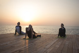 group of womans and man doing yoga on wooden pier, sunrise in the sea background