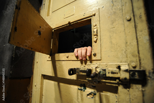 Interior of a bad condition prison cell seen through the door window Poster