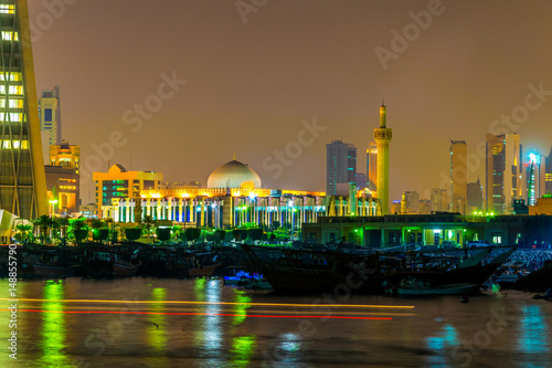 Poster The Grand mosque of Kuwait behind a dhow port near the Sharq souq in Kuwait druing night