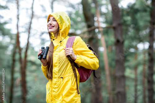 Young woman in yellow raincoat hiking with binoculars and backpack in the green pine forest. Bird watching in the forest