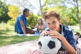 Smiling boy leaning on his football in picnic at park