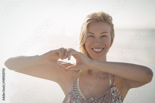 Portrait of woman making heart shape with hands at beach