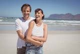 Portrait of cheerful couple embracing at beach