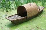 Old abandonned chinese bamboo boat in green water