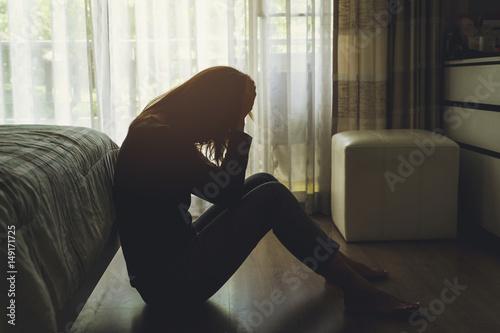 Foto Murales depressed woman sitting in the dark bedroom