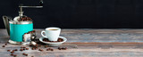 Coffee mill and cup of espresso. Concept of coffee drinking tradition. Selective focus. Wooden table, coffee beans. Black background. Wide panoramic image. Copy space.