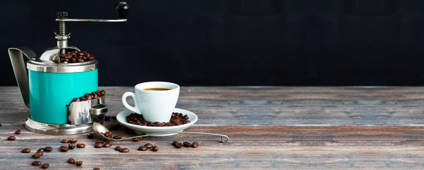Coffee mill and cup of espresso. Concept of coffee drinking tradition. Selective focus. Wooden table, coffee beans. Black background. Wide panoramic image. Copy space. © Studio Dagdagaz