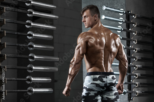 Rear view muscular man posing in gym, showing back and triceps. Strong male naked torso, working out