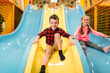Kids riding from childrens slides in game center - 149321165