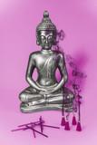 Estatua de buda con fondo rosa e incienso.