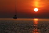 Segelboot ankert vor der Küste bei romantischem Sonnenaufgang