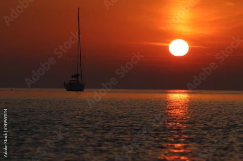 Keuken foto achterwand Rood paars Segelboot ankert vor der Küste bei romantischem Sonnenaufgang
