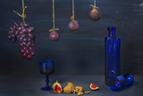 vintage style food still life with figs,walnuts, grapes, and old blue glass bottle
