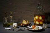 vintage style food still life with pickled eggs, bread, oil, vinegar and onions