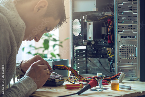Man repairman is trying to fix using the tools on the computer that is on a workplace in the office