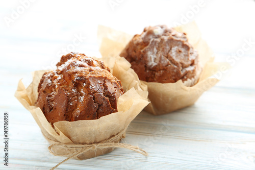 Tasty muffins on white wooden table