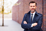 Portrait of confident businessman wearing coat standing outdoors with crossed arms - 149790510