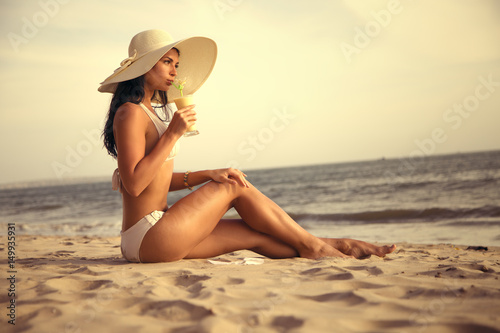 A bunnette model wearing white hat sitting on a beach sand drinking tropical coc Poster