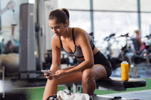 Póster Woman using phone at gym