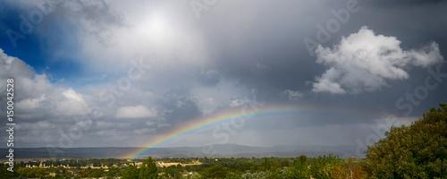 Panorama con un cielo nuvoloso e un arcobaleno