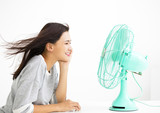 smiling woman cooling herself by electric fan - 150042796