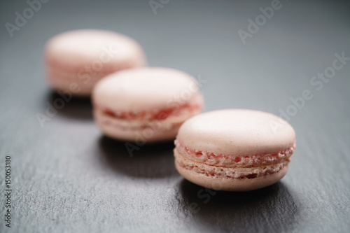 Spoed canvasdoek 2cm dik Macarons light pink macarons on slate background, shallow focus
