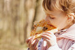 Beautiful little girl enjoying a delicious pizza in nature (food, hunger, pleasure) - 150098126