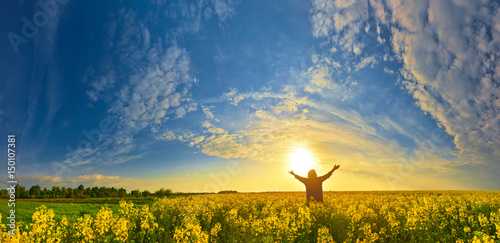 Woman on flower field at sunrise