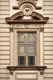 Antique window decorated with a sculpture of the head. Vilnius, Lithuania.