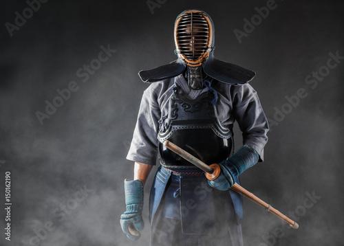 kendo-maestro-de-pie-en-armadura-tradicional-el-sostiene-la-espada-de-bambu-shinai