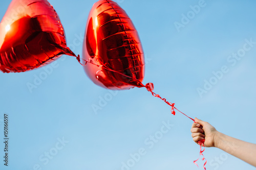 Poster beautiful heart balloons in hands against the sky