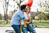 Fototapeta Young loving couple dating while riding bicycles in the city