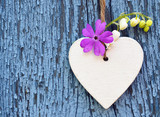 Decorative wooden heart with spring flowers on blue old wooden background.Spring decoration.Selective focus.