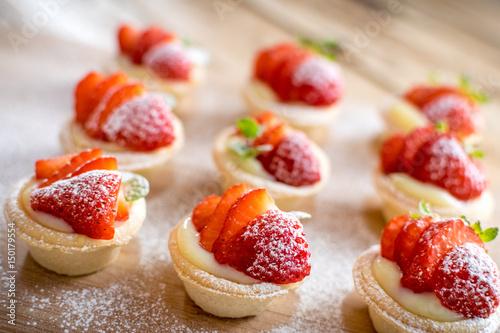 mini strawberry tarts on wood background