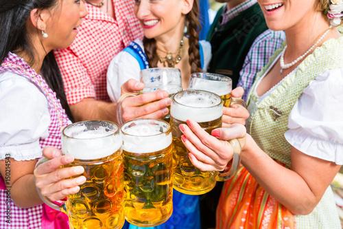 Freunde, zwei Männer, drei Frauen, stehen im Biergarten mit Maßkrügen