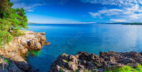 Aluminium Wonderful romantic summer afternoon landscape panorama coastline sea. Green trees at the edge of the coast harbor at crystal clear azure water.