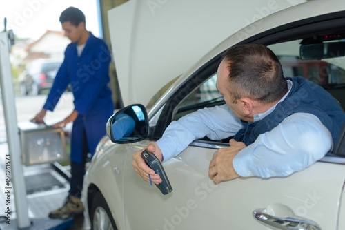 Poster Vehicle inspection being performed in garage