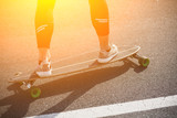 Man riding on longboard skate on road through forest or city. Man's legs on skateboard or longboard. Toned.