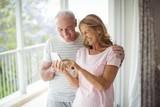 Happy senior couple using mobile phone in balcony