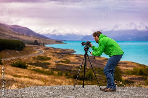 Travel photographer taking nature landscape pictures in New Zealand at sunset. Man shooting at Peter's lookout, famous tourist attraction at Pukaki Lake.