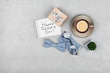 Fototapety Happy Fathers Day background with morning coffee cup, gift, glasses and bowtie on stone gray desk top view in flat lay style.