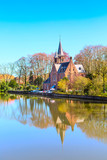 Minnewater lake panorama, reflection of gothic Flemish style house, blue sky, spring in Bruges, Belgium